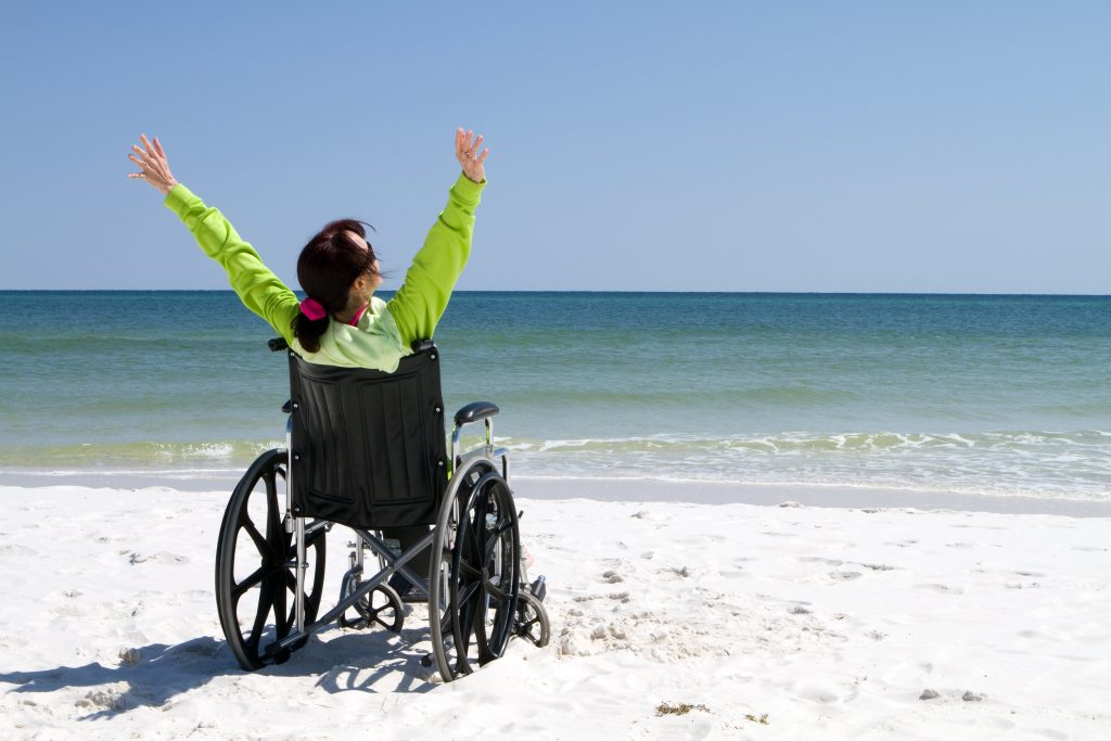 Woman with arms raised celebrates her achievement and success in the sunshine even with her disabilities in a wheelchair.